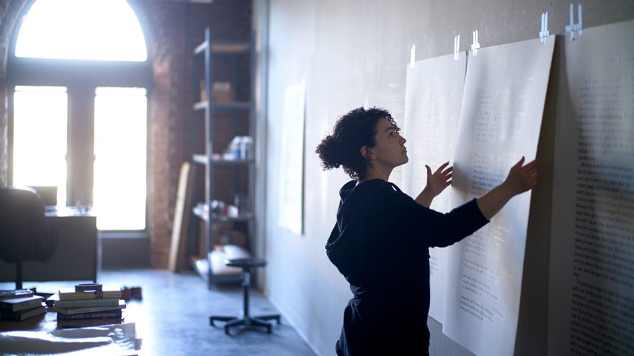 تصویر زن جوان در حال نصب پوستر